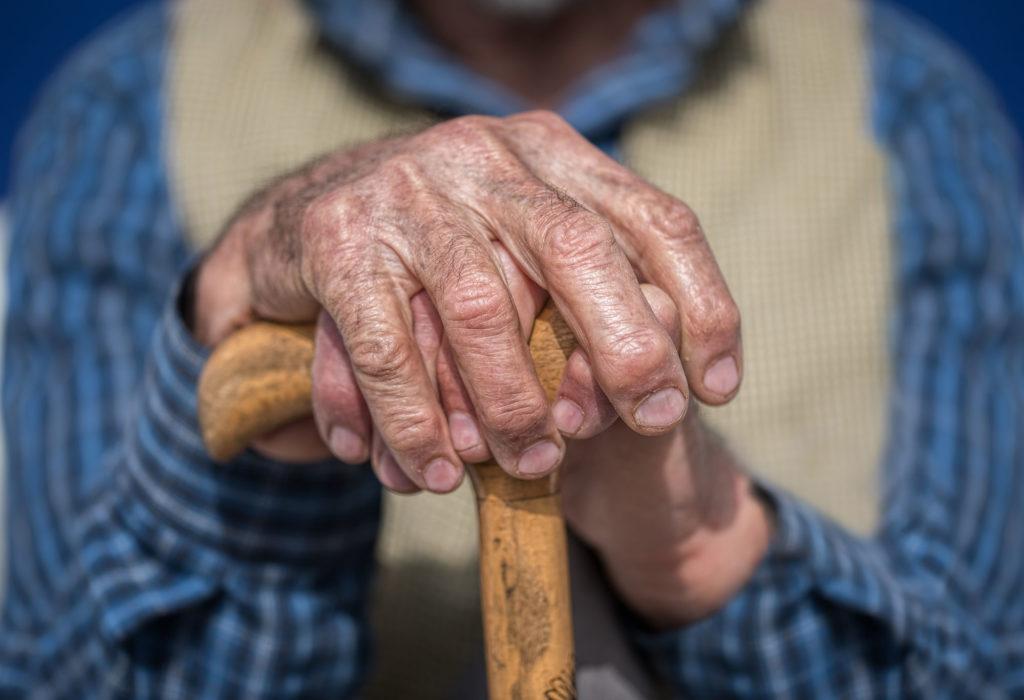 hands of an elder on a cane